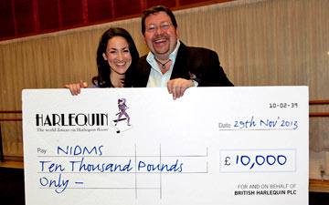 DanceUK's Erin Sanchez receiving the cheque from Mark Rasmussen of Harlequin Floors.© DanceUK. (Click image for larger version)
