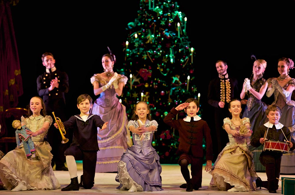 Amy Pollock as Clara, Jamie Campbell as Fritz with Party Children in Peter Darrell's <I>The Nutcracker</I>.<br />© Andy Ross. (Click image for larger version)