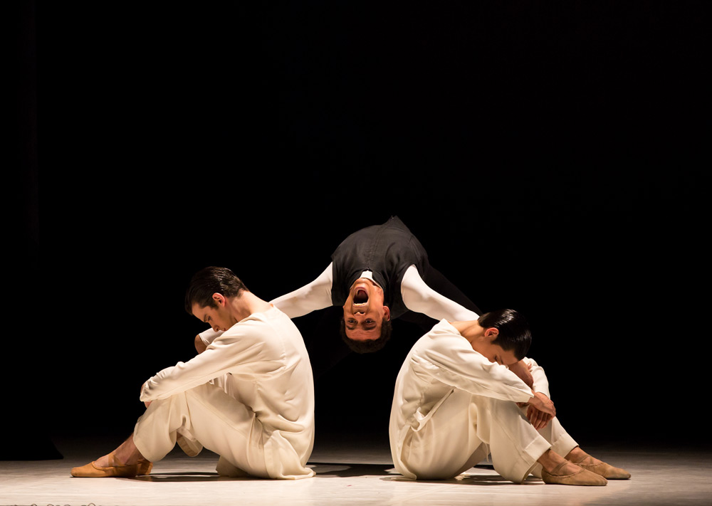 Isaac Lee-Baker as Friar Laurence with Jeremy Curnier and Kevin Poeung as the two acolytes in Jean-Christophe Maillot's Romeo and Juliet.© Andy Ross. (Click image for larger version)