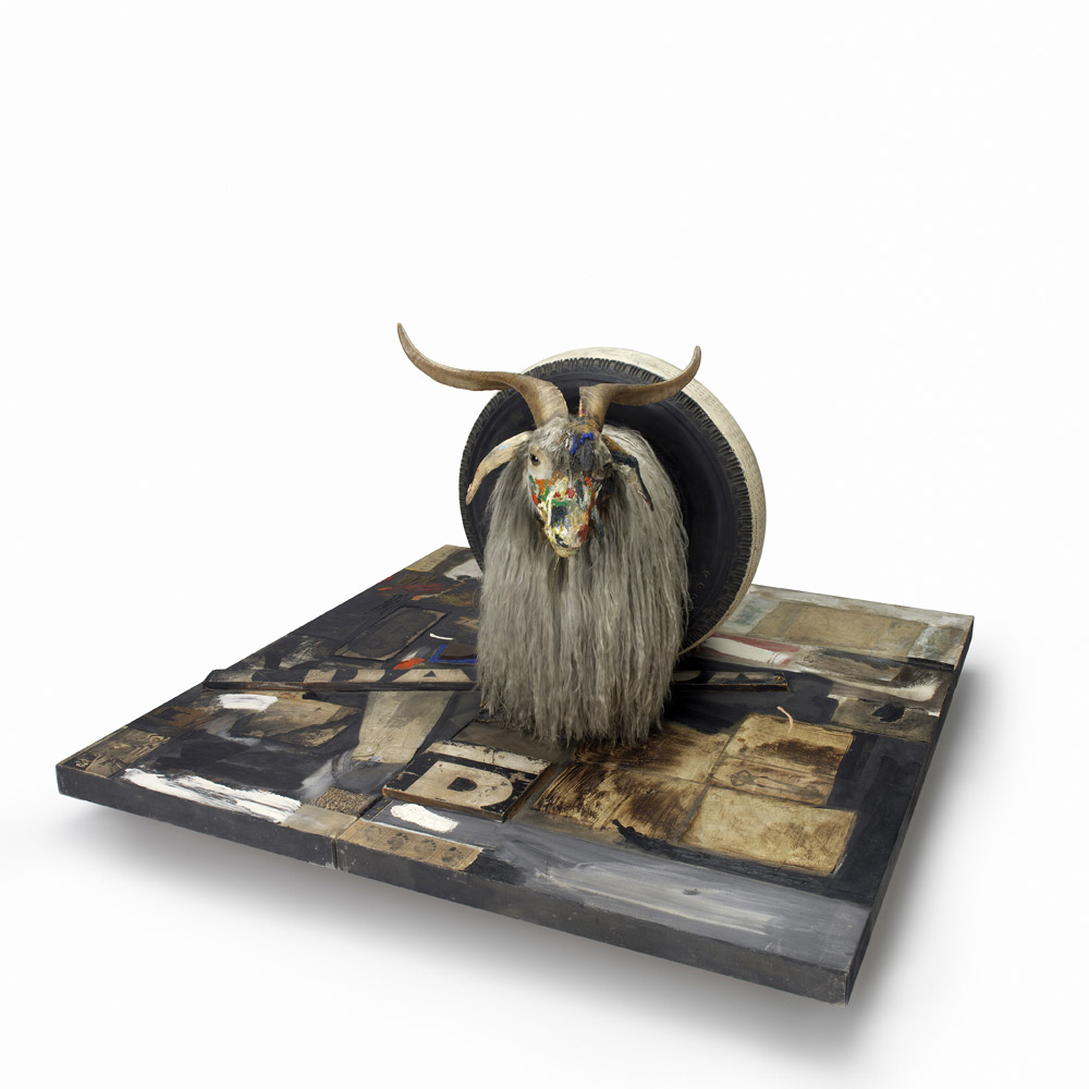Robert Rauschenberg: Monogram (1955-59).Combine: oil, paper, fabric, printed reproductions, metal, wood, rubber shoe-heel, and tennis ball on two conjoined canvases with oil on taxidermied Angora goat with brass plaque and rubber tire on wood platform mounted on four casters.106.7 x 135.2 x 163.8 cm. Moderna Museet, Stockholm. Purchase with contribution from Moderna Museets Vänner/The Friends of Moderna Museet.© Robert Rauschenberg Foundation, New York. (Click image for larger version)