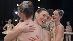 Tiler Peck hugging Ashley Laracey, with Unity Phelan at right, after the finale of George Balanchine's Divertimento No. 15.© Philippe Le Sourd. (Click image for larger version)